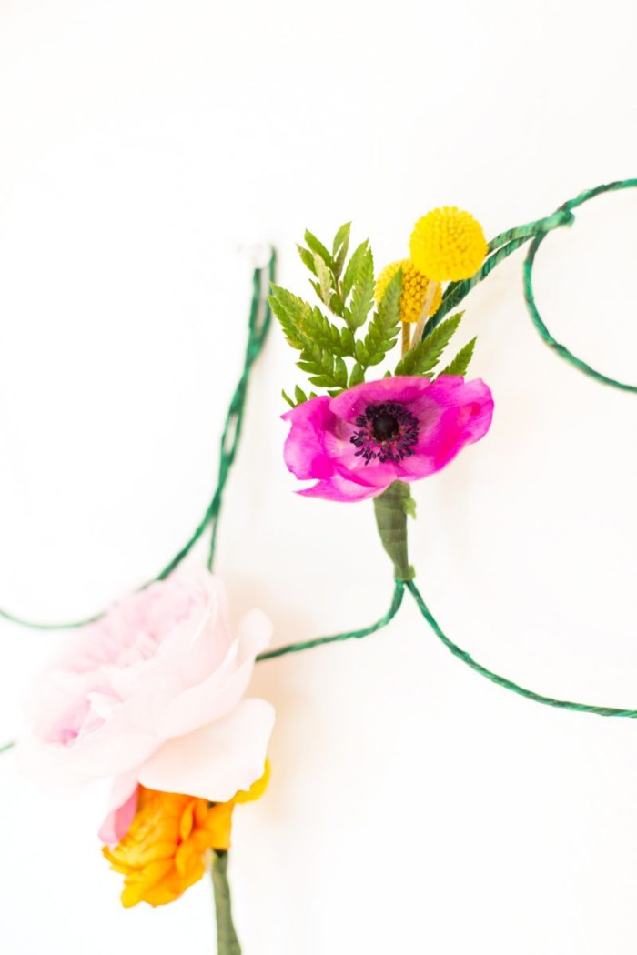 close up of purple, pale pink and yellow flowers, attached to a thin green wire, diys for girls, on a white background