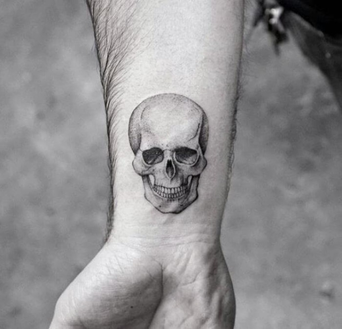 anatomically correct human skull, tattooed in black and grey, on a man's wrist, tattoos with deep meaning, memento mori, photo in black and white