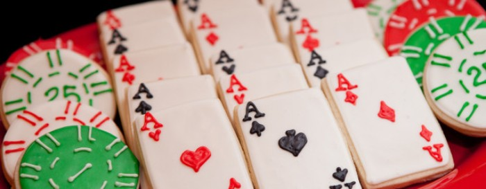 50th birthday party ideas for men, selection of round and rectangular cookies, decorated with white and black, green and red frosting, and made to look like playing cards and poker chips