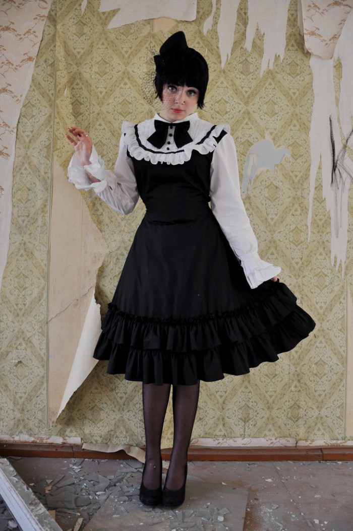 old ripped ornamental wallpaper, behind a young woman, in a black wig, wearing a black and white dress, with frills and a bow, define lolita