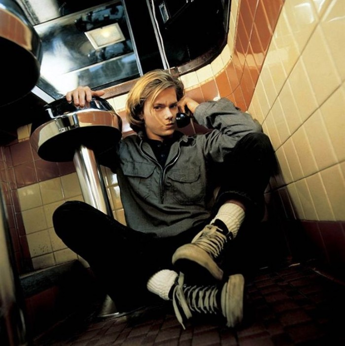 actor river phoenix, sitting on the floor of a retro diner, holding a telephone receiver, and leaning on a bar stool, 90s bands and iconic celebrities