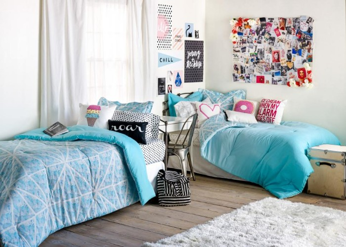 beds with blue duvets, and colorful cushions, in a room with white walls, and a wooden floor, cute teen rooms, posters and a board with photos