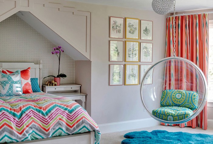teen bedrooms, bed with a multicolored duvet, a round swing, made from clear plastic, window with orange patterned curtains, and nine framed artworks