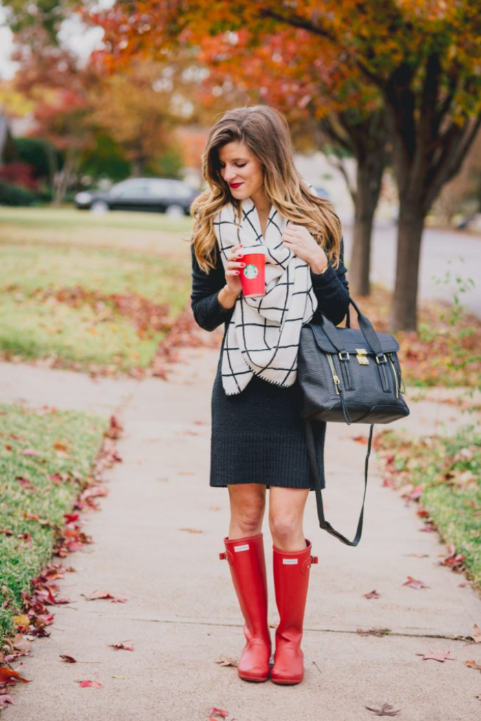 wellington boots in red, combined with a dark grey jumper dress, and a white and black, checkered blanket scarf, comfy outfits, black leather bag