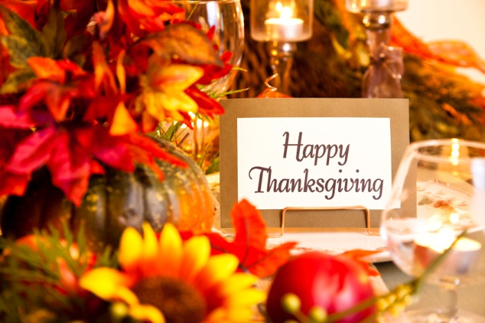 card with the words happy thanksgiving, placed on a table, decorated with multiple faux flowers, in red and yellow and orange, thanksgiving message to employees
