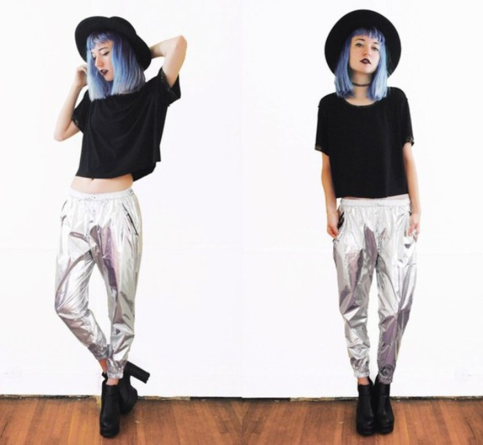 metallic trousers in silver, worn with a black cropped t-shirt, and high-heeled black leather ankle boots, 80s grunge attire, on a young woman, with light blue hair, and a black felt hat