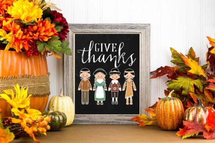 drawing featuring pilgrims and indians, with the words give thanks, on a blackboard, with a grey wooden frame, surrounded by fall-themed decorations