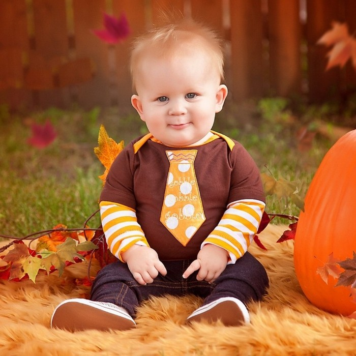 necktie shape in orange, with white polka dots, sewn on a brown t-shirt, worn over a white and orange striped jumper, by a smiling baby boy, baby's first thanksgiving outfit, dark blue jeans