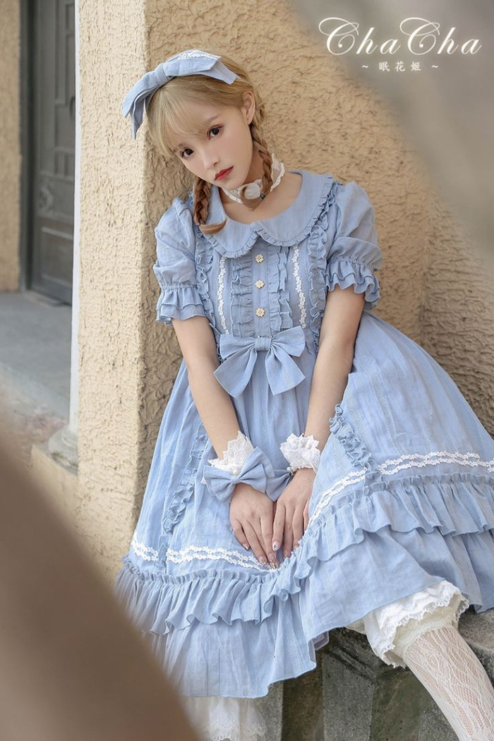 baby blue dress, with lots of frills, a peter pan collar, lace trims and small bows, what is lolita, worn by a slim young woman, with dark blonde pigtails