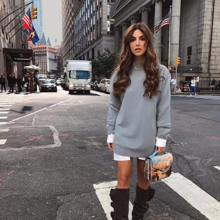 baggy and long, pale grey jumper, over an oversized white shirt, thanksgiving outfits for women, brunette woman with long hair, wearind tall suede, dark brown boots