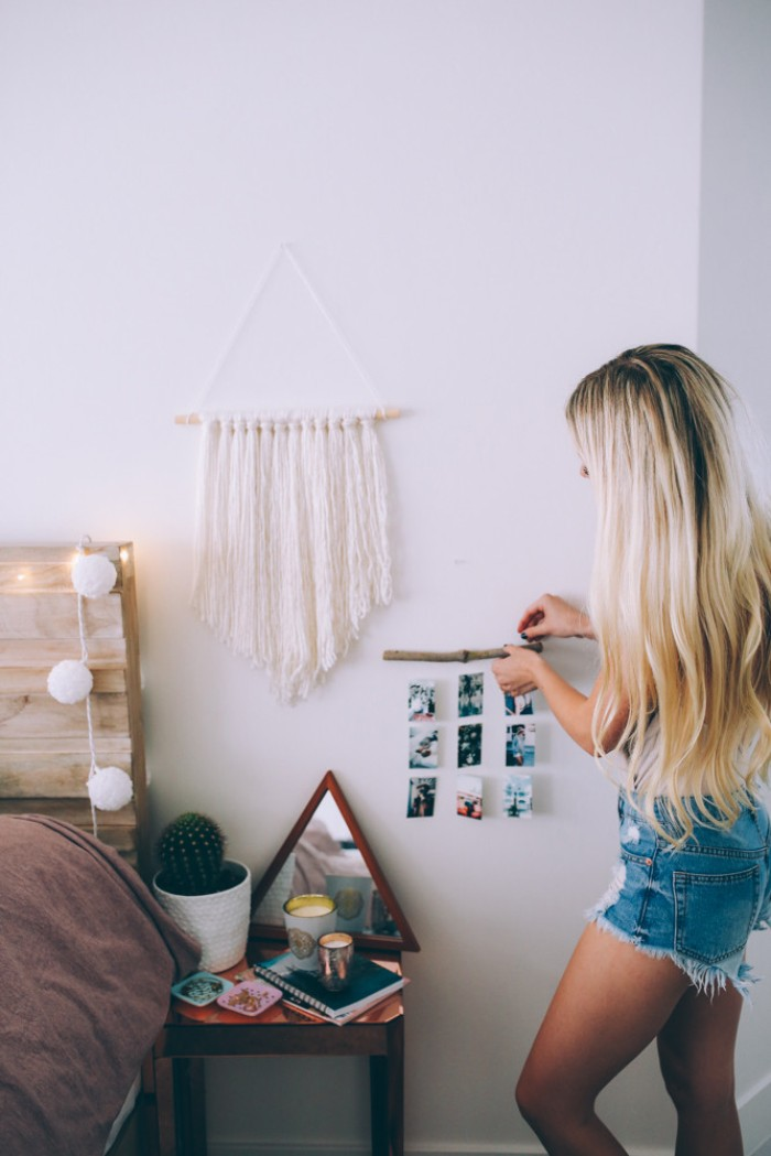 blonde woman with long wavy hair, attaching a small wooden stick, decorated with nine photos, tied on pieces of string, to a white wall, cute teen rooms, marcame wall decoration in white nearby