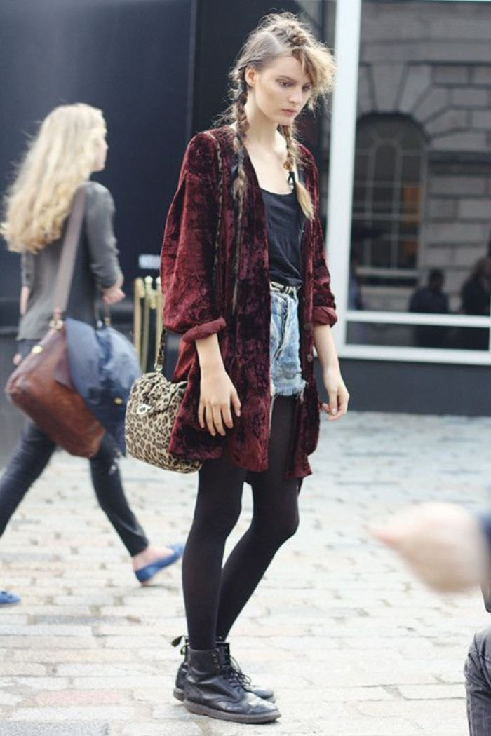 velvet cardigan in burgundy, worn over a black top, black opaque tights, and light blue cutoff denim shorts, by a slim young woman, with braided hair, and black leather combat boots