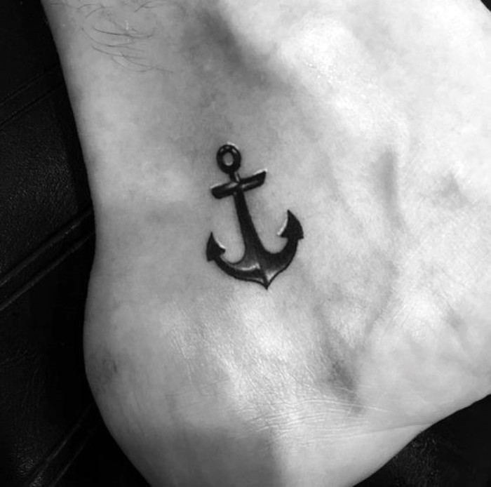 another version of an anchor tattoo, in black with white details, small symbolic tattoos, steadfastness and family, on a man's foot, close to his ankle and sole