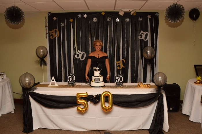 blonde woman in a black dress, smiling while standing next to a festively decorated table, 50th birthday party ideas for mom, balloons and a cake