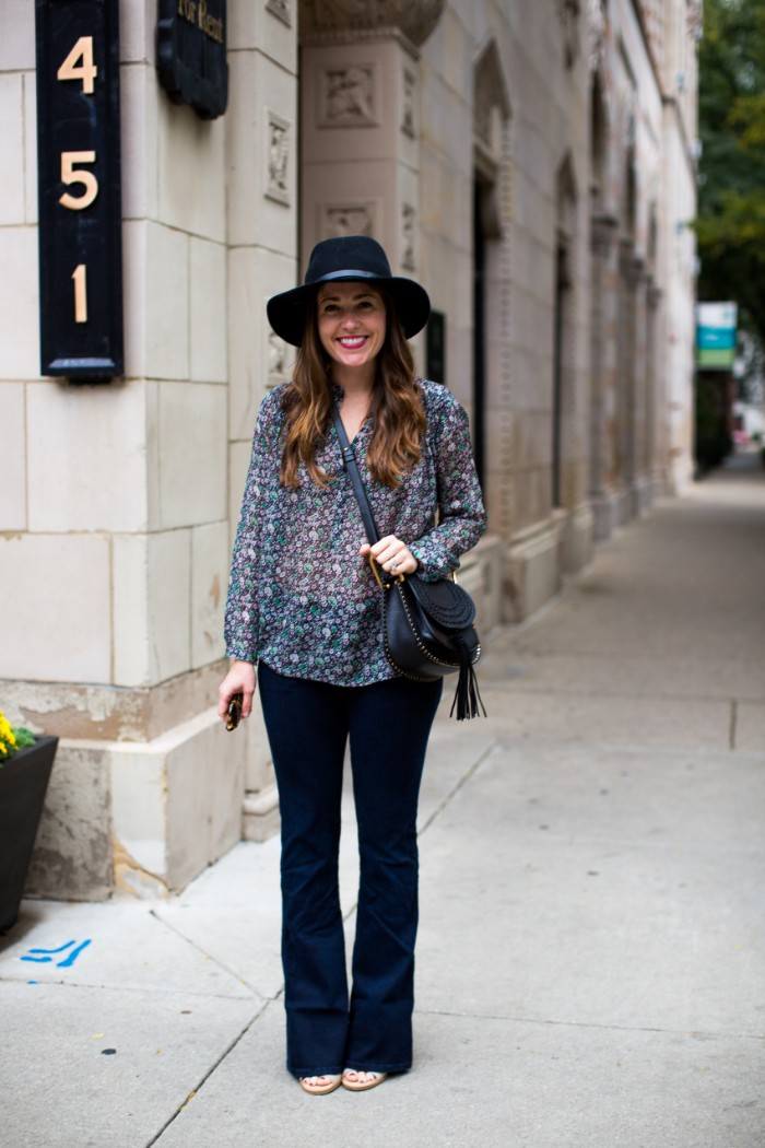 patterned semi-sheer blouse, and slightly flared dark blue jeans, worn by a smiling brunette woman, thanksgiving outfits, with black felt hat, and black cross body bag