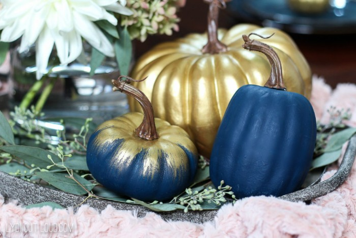 three pumpkins painted in dark blue, and metallic gold paint, thanksgiving card messages, white flowers and green plants in the background