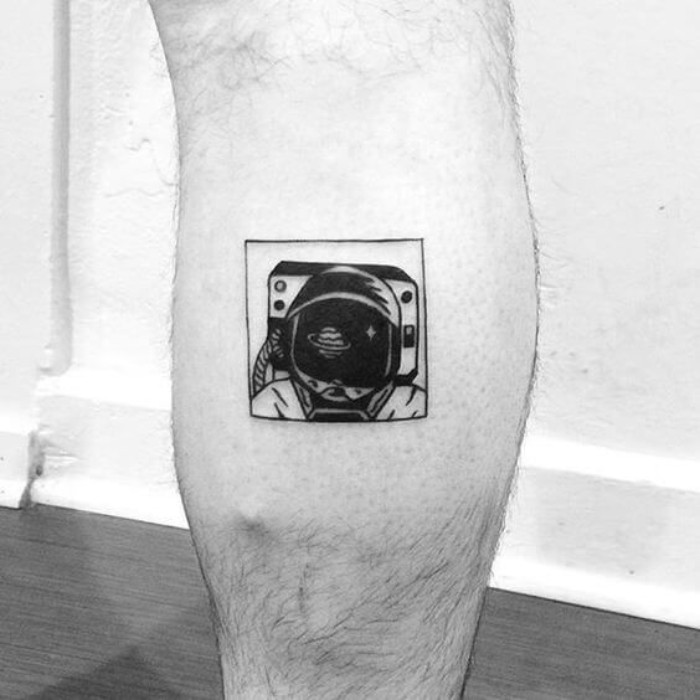 vintage austronaut's head, with a helmet, tattooed in black ink, inside a square, on a person's lower leg, small tattoos with meaning, black and white image