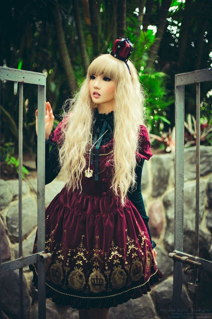 velvet dress in burgundy, with gold print, worn over a black lacy shirt, by a japanese lolita, in a long blonde wig, decorated with a miniature crown