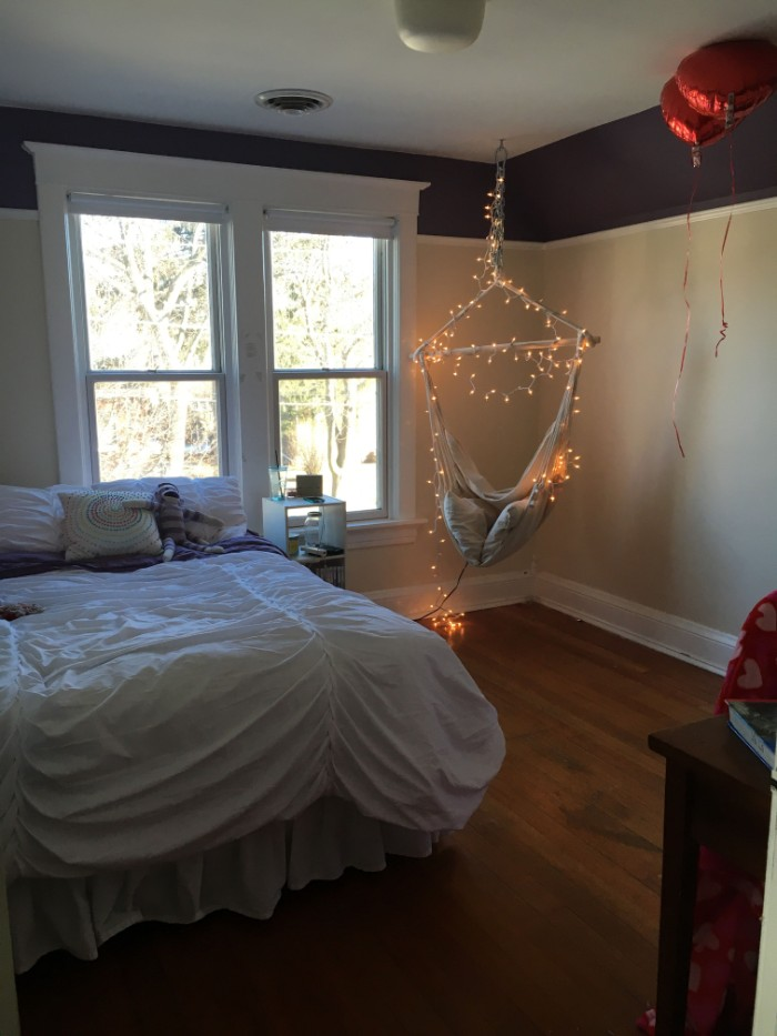 window with white frames, in a room with a bed, and a swing, decorated with lit string lights