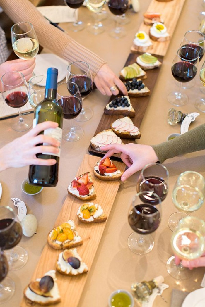 narrow wooden boards, containing a selection of tapas, surrounded by filled and empty wine glasses, 50th birthday themes, wine and tapas tasting idea