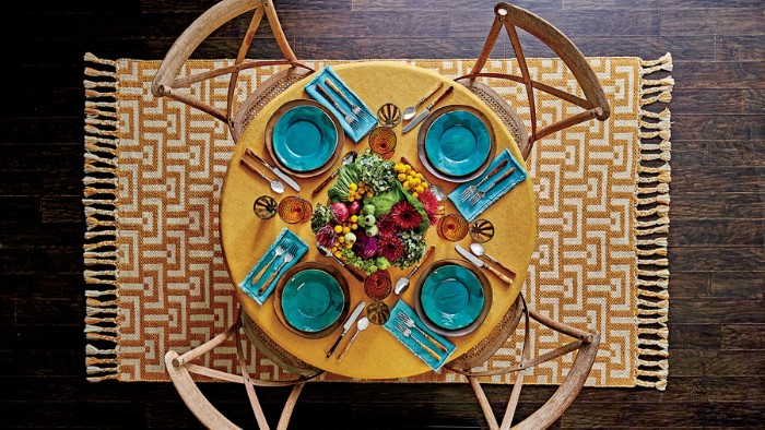yellow round table, with four seats, featuring teal plates and napkins, thanksgiving dinnerware, centerpiece with fall vegetables