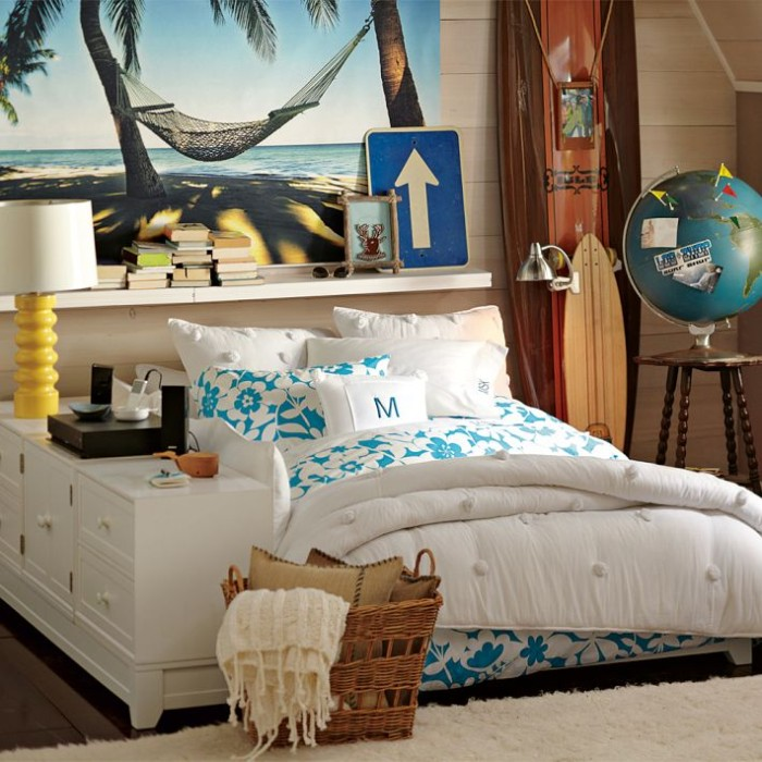 floral duvet and pillow covers, in white and teal, on a bed in a spacious room, with surfing boards, and a model globe, large photo of a hammock on a beach, covering one wall, cool beds for teens