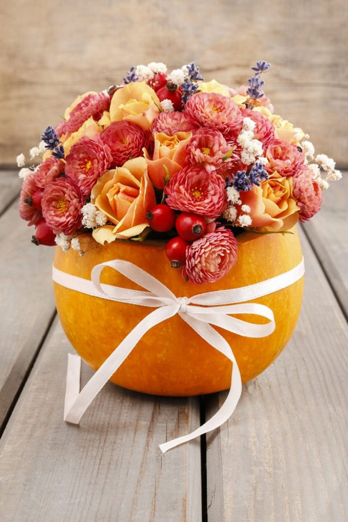 ribbon in white, tied in a bow around a large, hollow orange pumpkin, filled with red flowers, pale orange roses, lavender and small white blossoms, cheap centerpiece ideas, on a pale grey wooden surface