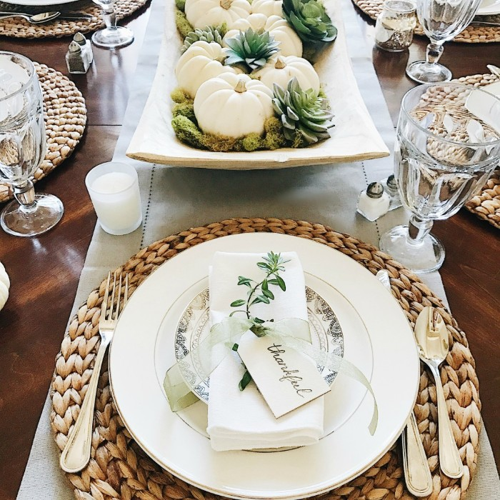 sprig of a green plant, tied to a folded white napkin, with a sheer silber ribbon, featuring a small label saying thankful, placed on a plate, thanksgiving table setting, round rattan table mats