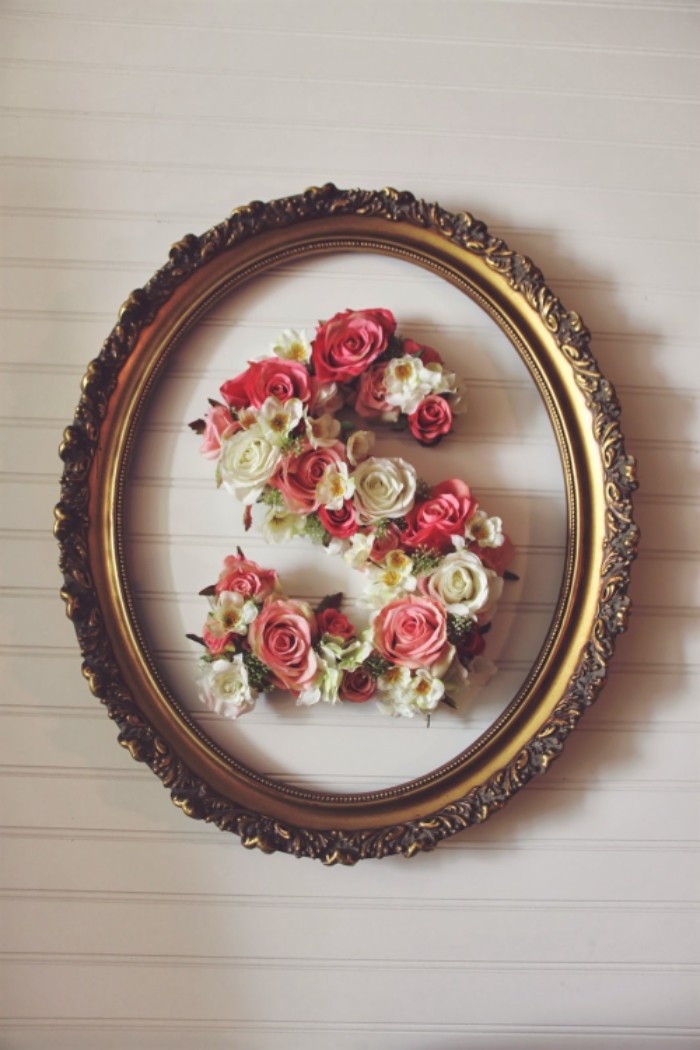 oval frame in gold, with ornamental details, containing the letter s, decorated with faux flowers, pink and white roses, white and yellow blossoms