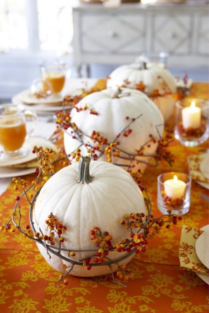 wreaths made from thin branches, with tiny orange berries, wrapped around three white pumpkins, placed on an orange and yellow patterned tablecloth