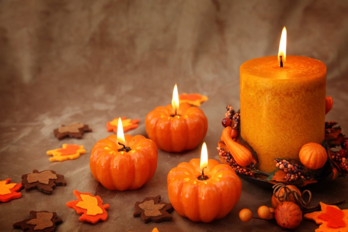 small lit candles, shaped like pumpkins, near a larger, cylinder shaped orange candle, thanksgiving card messages, small decorative autumn leaves, made from felt