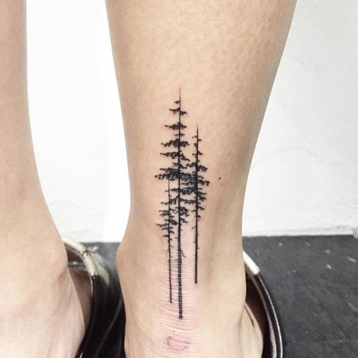 simple design featuring three tall, and narrow pine trees, tattooed in black, on the back of a person's ankle