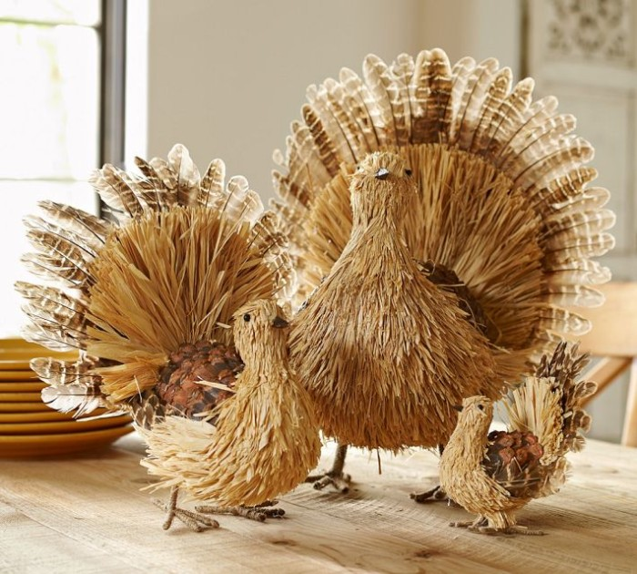 large medium and small turkey decorations, made from wicker, wood and and real turkey feathers, placed on a pale beige wooden table