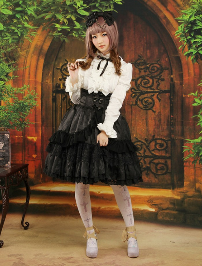 mural of an antique wooden door, behind a girl, dressed in a black and white lolita outfit, blouse with a frilly bib detail, and a black ribbon, tiered skirt with flounces