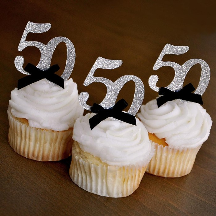 silver glitter toppers, shaped like the number 50, and featuring small black bows, decorating three vanilla birthday cupcakes, with creamy white frosting