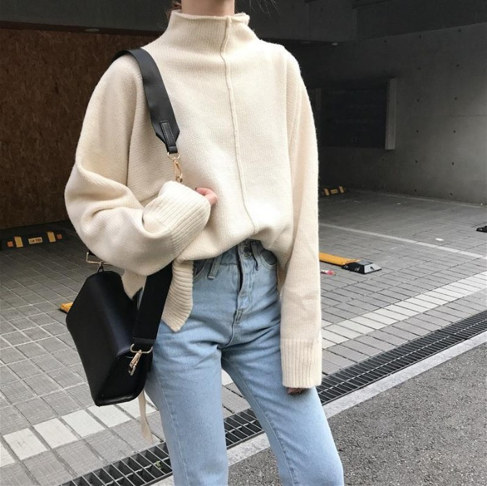 cream turttle neck jumper, oversized and featuring a rim detail, running down its front, worn half tucked in pale blue, high waisted jeans, with a black leather shoulder bag, grunge definition