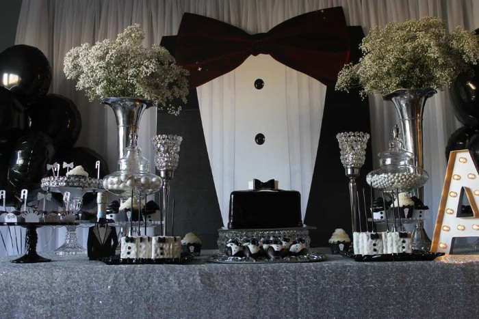 wall decoration shaped like a large tuxedo, near a table with a black cake, various black and white sweets, and two bouquets of small white flowers