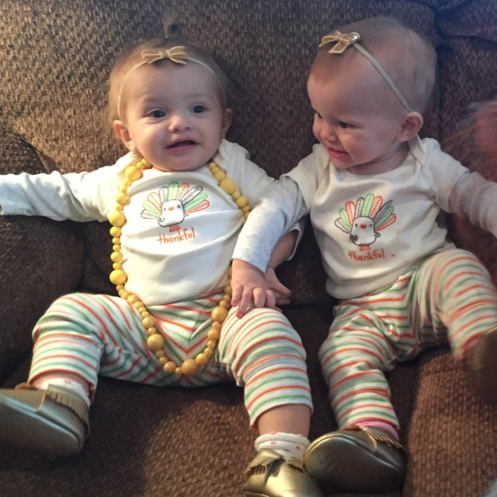 pair of babies, dressed in identical clothes, white jumpers featuring cartoon turkey prints, baby girl thanksgiving outfit, striped trousers in light green, white and orange, shiny gold soft shoes