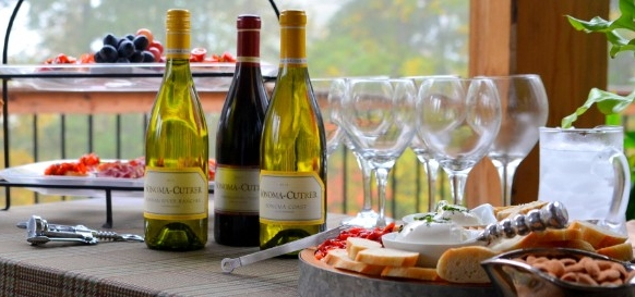 red and white wine bottles, near several plates, featuring assorted canapes, 50th birthday party ideas, clear wine glasses and fruit
