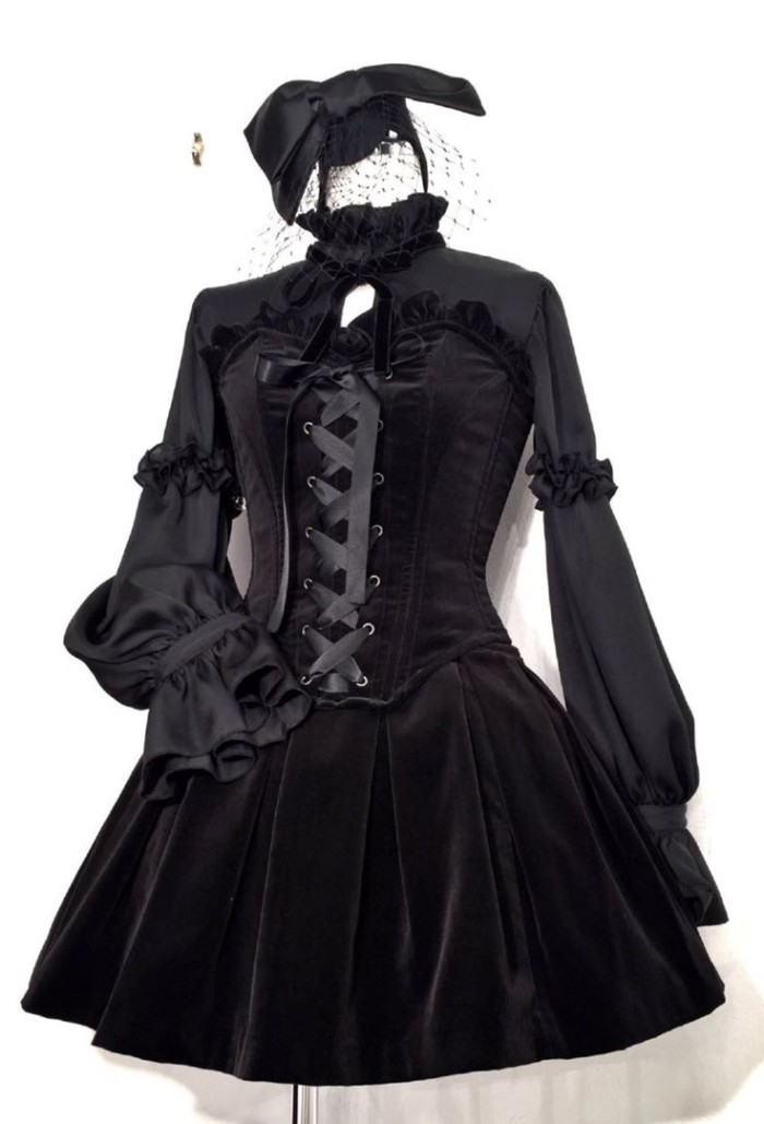 velour lolita style dress in black, with frilly sleeves, and a lace up corset detail, small face veil made from black mesh, and a large black hair bow