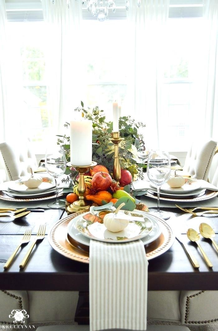 well lit room with a black table, set for a festive meal, stacked plates, decorated with small white pumpkins, gold cutlery and striped napkins, thanksgiving dinnerware, candles and flowers, fruit and gourds