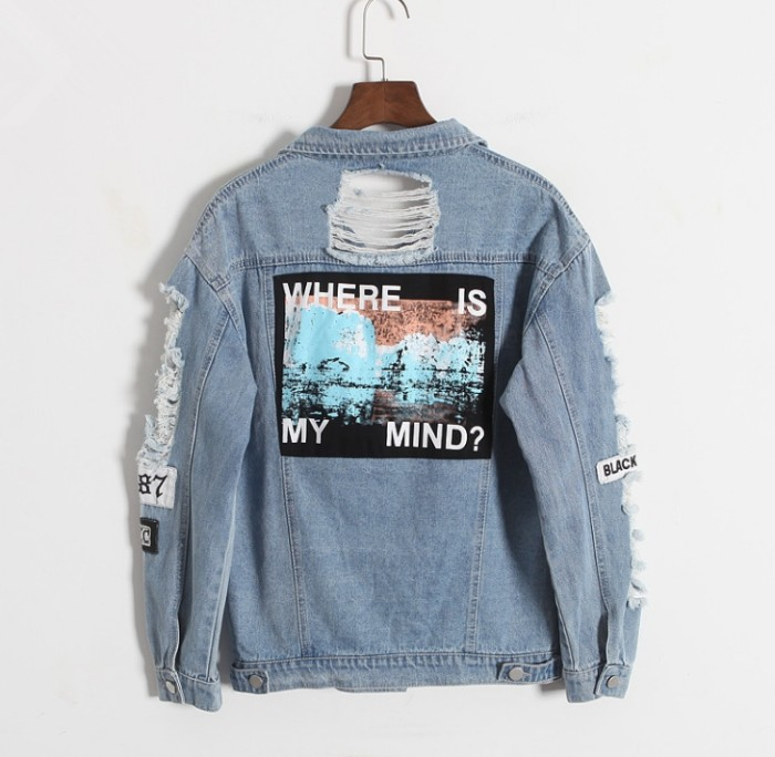 denim jacket in light blue, with several large rips, and a few patches, featuring a graphic print on its back, on a wooden hanger