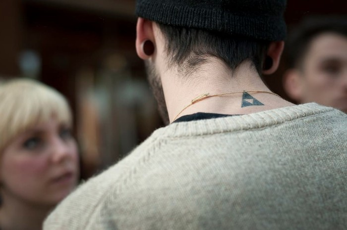 man dressed in a pale grey sweater, with his back to the camera, a black triangle tattoo, with a smaller, white reversed triangle inside, small tattoos for men, on the back of his neck