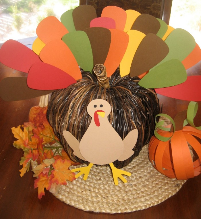 paper cutout of a turkey, stuck on a whicker pumpkin ornament, with a tail made from pieces of paper in different colors, turkey decorations, faux fall leaves, and a paper pumpkin nearby