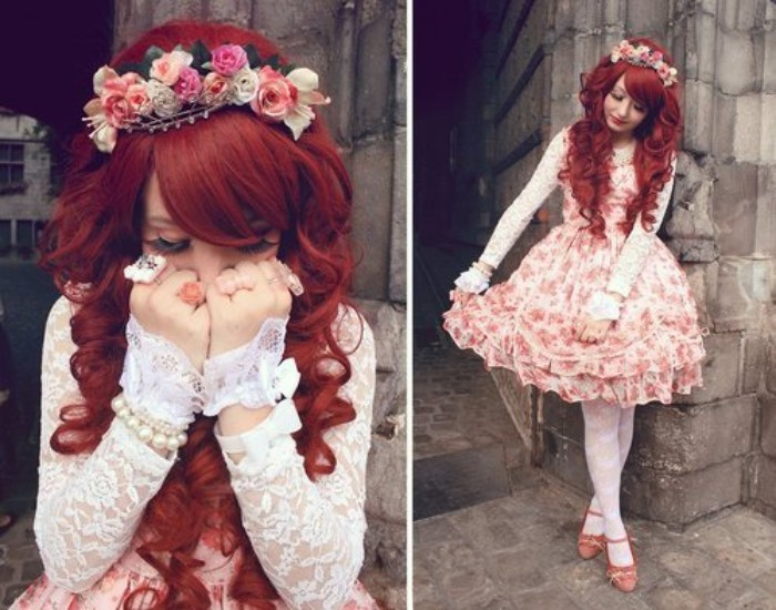 red wig with curls and side bangs, worn by a young woman, in a floral pink sweet lolita dress, with white lace sleeves