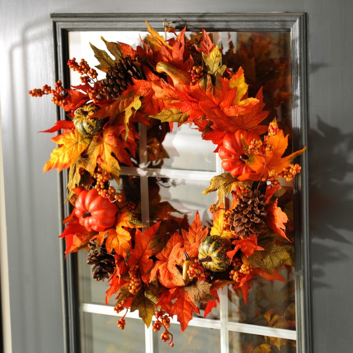 fall wreath made from faux leaves in yellow, orange and pale green, thanksgiving greeting message, decorated with pine cones, small fake pumpkins, and tiny orange berries