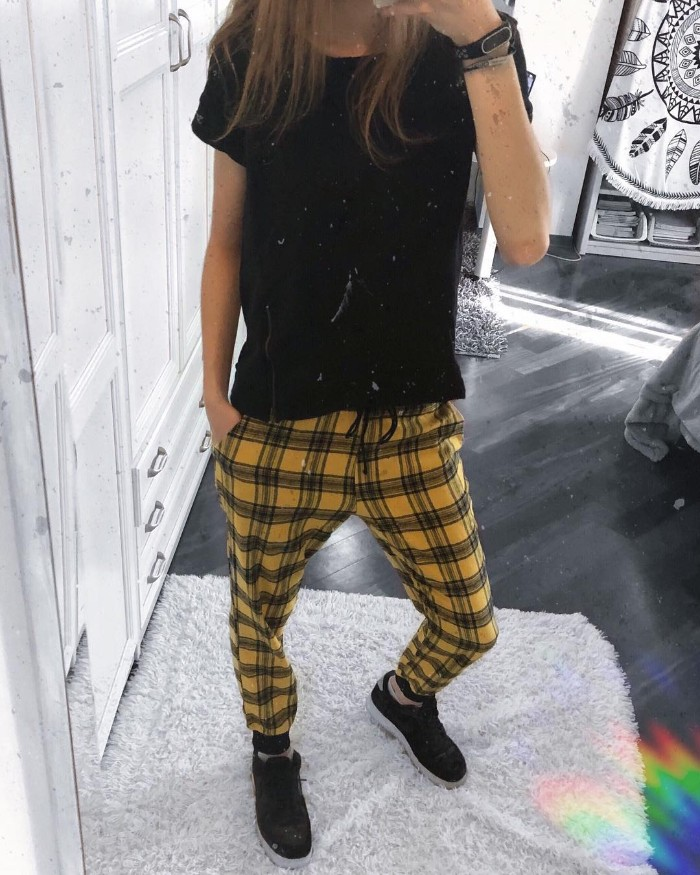 slim woman dressed in a black t-shirt, yellow checkered trousers, and black sneakers, grunge definition, taking a mirror selfie