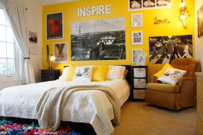 armchair in beige, and a large bed in white, near a yellow wall, decorated with posters, framed images and words