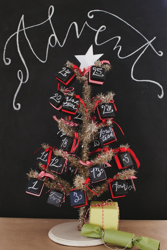 small faux christmas tree in gold, decorated with black cube-shaped boxes, featuring numbers written in white, and red bows, diy advent calendar