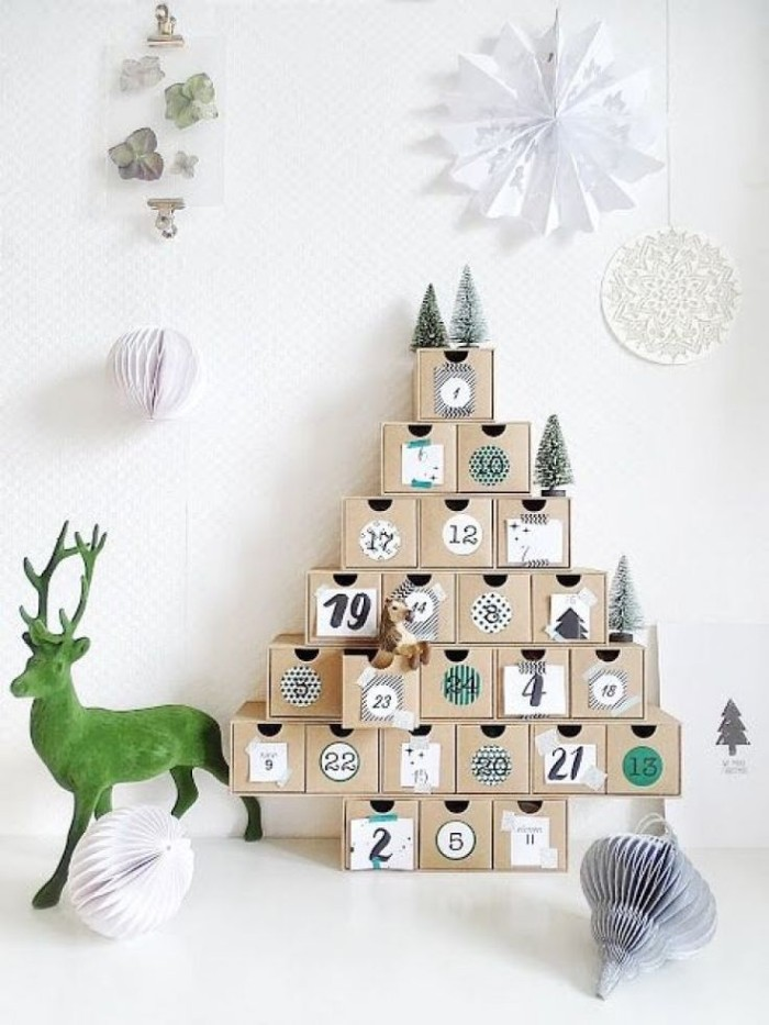 reindeer figurine in green, next to an advent calendar, made from multiple, numbered pale beige, cube-shaped boxes, stacked in a christmas tree shape